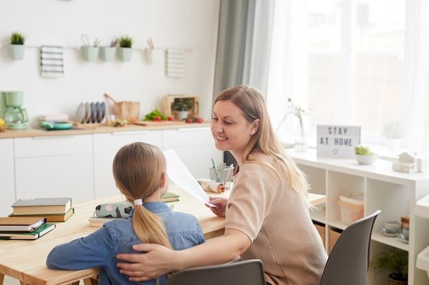 Портрет заботливой улыбающейся матери, обнимающей маленькую девочку, сидя за столом и помогая ей учиться дома, скопируйте пространство