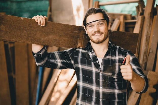 木のワークショップで笑っている大工の若い中小企業の家具店の所有者の肖像画は、プロの熟練した実在の人々の手工芸職人に見えます。