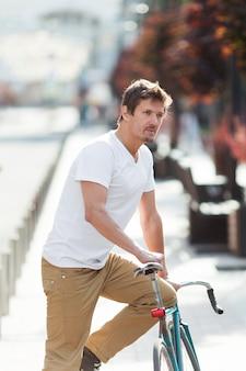 カジュアルな男性乗馬自転車の屋外の肖像画