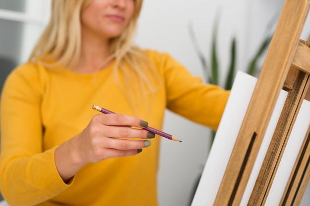 自宅で絵画のカジュアルな女性の肖像画