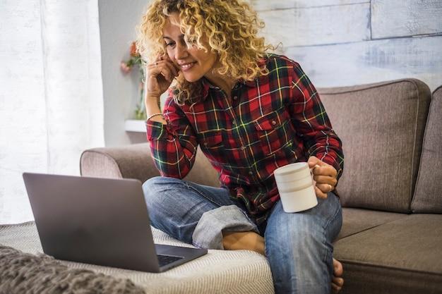 自宅で白人の大人の美しい女性の肖像画は、ソファに座ってラップトップコンピューターを使用します