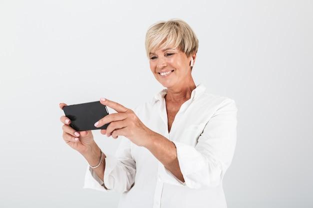 イヤポッドを身に着けて、スタジオで白い壁に隔離された携帯電話を保持している短いブロンドの髪を持つ白人の大人の女性の肖像画