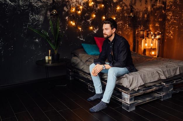 現代のbadroomで彼のベッドに座っているカジュアルな服を着ている白人のひげを生やした男の肖像画。
