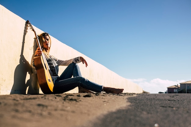 白人の美しい金髪の歌手アーティストの肖像画は、彼女に日光を当ててカメラを見ながら通りに座っています。風の強い夏の日の自然と街の素敵な表面