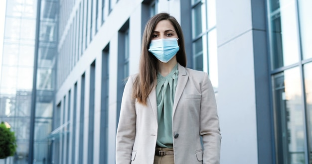 屋外に立っている医療マスクの白人の美しいスタイリッシュな女性の肖像画。呼吸保護の実業家。