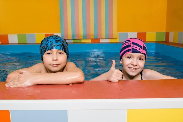 Портрет кавказского мальчика и девочки в бассейне
