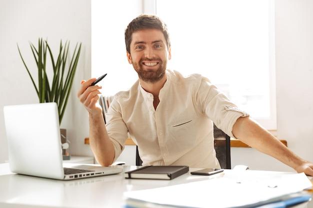 明るいオフィスに座っている間、ラップトップで作業している白いシャツを着ている白人実業家30代の肖像画
