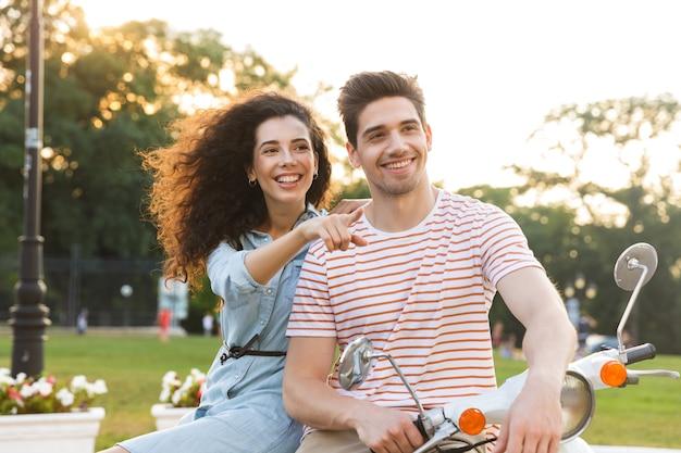 都市公園でバイクに一緒に座っている白人カップルの肖像画