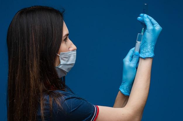 의료 가운, 푸른 의료 장갑 및 특수 마스크에 검은 머리를 링 백인 여성의 초상화는 의약품 주사기를 보유하고