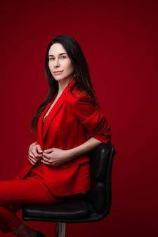 赤いオフィススーツ、黒い靴が黒い椅子に座っている長い黒髪の白人女性の肖像画