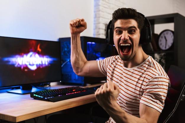Портрет кавказского геймера, кричащего и радующегося, играя в видеоигры на компьютере в наушниках