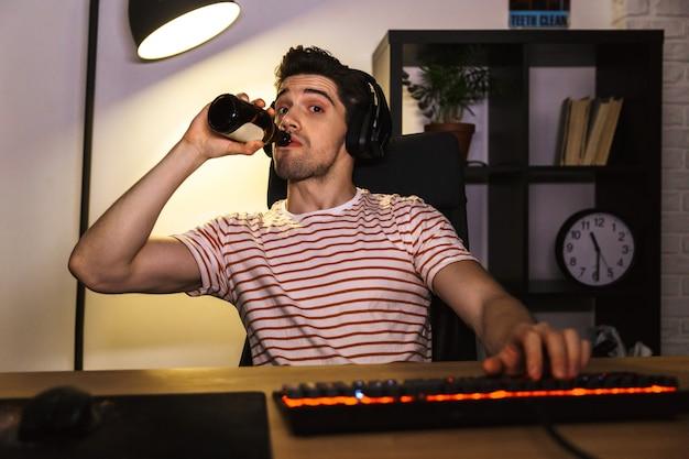 Портрет кавказского геймера в наушниках, пьющего пиво, сидя за столом с компьютером в комнате и смотрящего в камеру