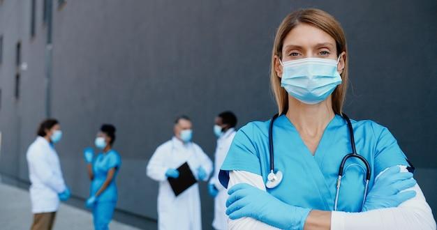 カメラを見ている医療マスクと手袋で白人の格好良い女性医師の肖像画。呼吸保護の女性医師のクローズアップ。背景に多民族の医師。ドリーショット。