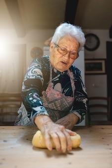 파스타 또는 다른 전통적인 조리법을 준비하기 위해 반죽을 반죽하는 백인 할머니의 초상화.