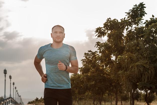 훈련 및 일몰 동안 아스팔트 트랙에서 실행되는 파란색 티셔츠와 검은 색 반바지에 백인 남자의 초상