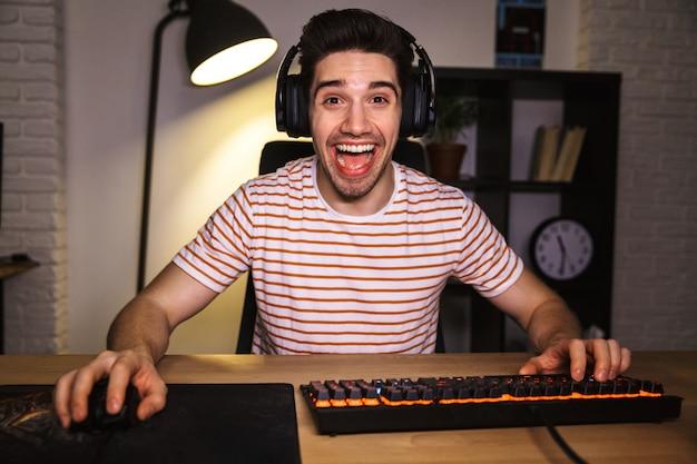 Портрет кавказского парня в наушниках улыбается, глядя на компьютер, и использует красочную клавиатуру с подсветкой