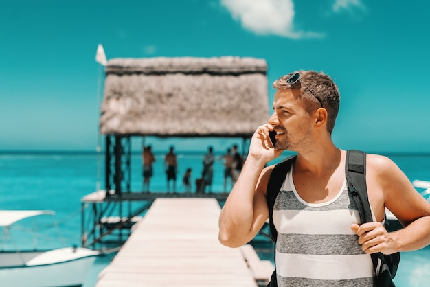 ドックに立って、よそ見しながらスマートフォンを使用して白人のハンサムな男の肖像。夏の休日のコンセプトです。