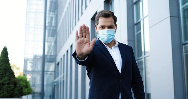 屋外に立って、手で停止ジェスチャーを示す医療マスクの白人ハンサムなスタイリッシュな男の肖像画。社会的距離の概念。呼吸保護のビジネスマン。