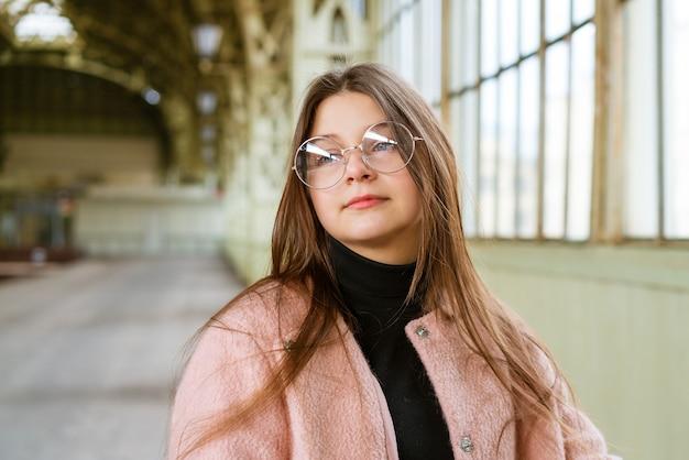 ピンクのコートと黒のタートルネックスタンドで長い髪のメガネで白人の幸せな女の子の肖像画...