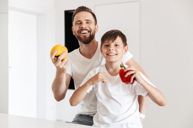 Портрет кавказских здоровых отца и сына, улыбающихся вместе дома, держа в руках свежие сладкие бумаги