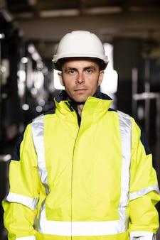 ヘルメットをかぶってカメラに自信を持ってポーズをとる白人の重工業エンジニア労働者の肖像画