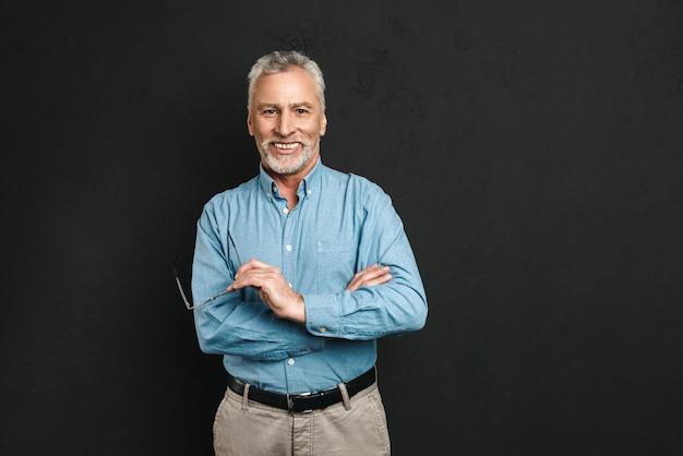 灰色の髪とひげを笑顔で腕を組んで立っている間眼鏡を押しながら黒い壁に分離された白人男性年金受給者60年代の肖像画