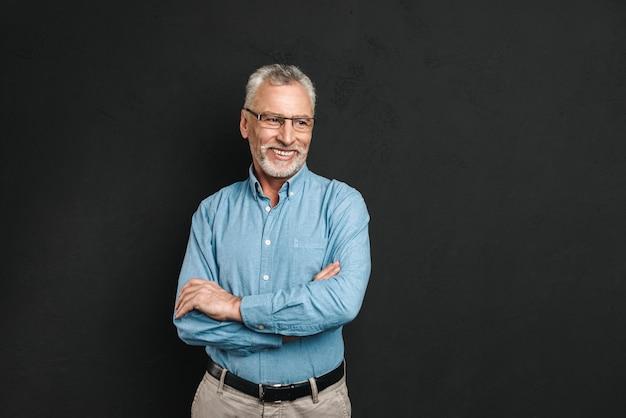 灰色の髪とひげの笑みを浮かべて、腕を組んで立っている間よそ見と黒い壁に分離された60代の白人男性年金受給者の肖像画