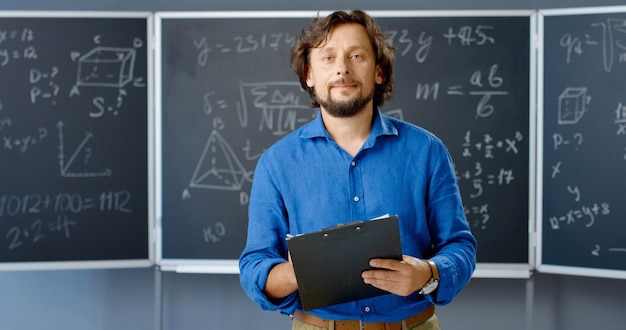 Портрет кавказского учителя-мужчины, стоя в классе с папкой в руках, глядя на камеру. математические формулы и законы на фоне. математик-преподаватель человек работает в школе или колледже.