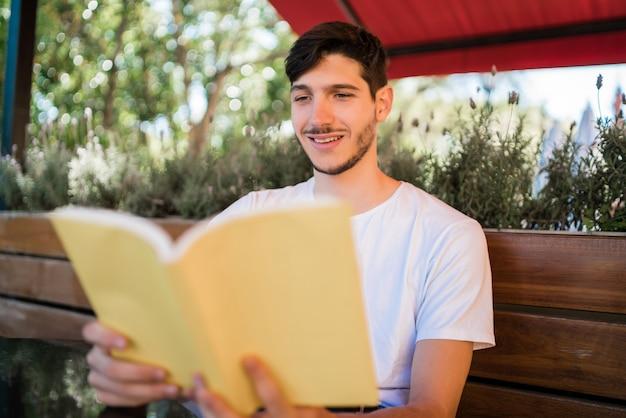 自由な時間を楽しんで、コーヒーショップで屋外に座って本を読んでいる白人男性の肖像画。ライフスタイルのコンセプト。