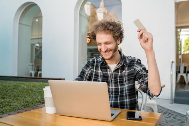クレジットカードを保持し、ラップトップを使用してコーヒーショップでオンラインショッピングをする白人男性の肖像画。オンラインショッピングとライフスタイルのコンセプト。