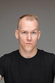 회색 벽에 고립 된 의심과 검은 티셔츠에 백인 남자의 초상화