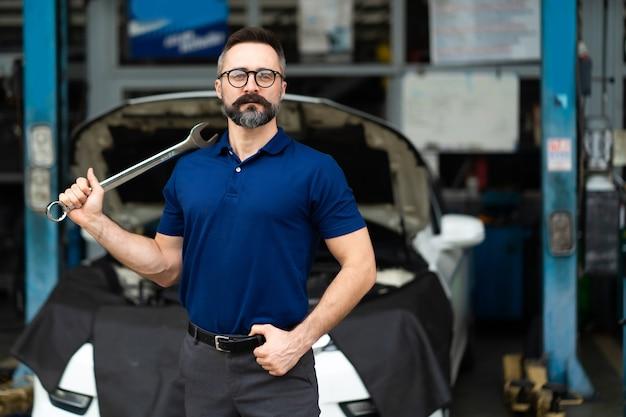 카메라와 손에 큰 렌치 도구에 웃는 백인 남자의 초상화. 자동차 수리 차고에서 일하는 전문 정비사.