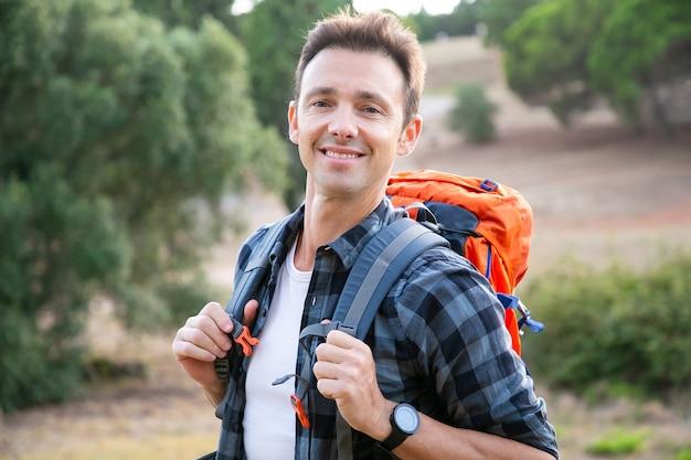 立っている、笑顔の白人男性の肖像画。自然を楽しみ、バックパックを背負ってポーズをとる幸せなハイカー。観光、冒険、夏休みのコンセプト