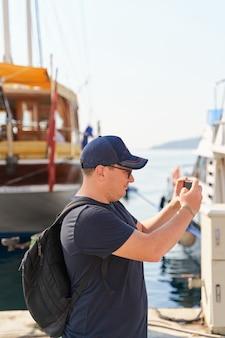 배낭 스마트 폰 사진 만들기 백인 남자의 초상화. 요트 해변 여행.