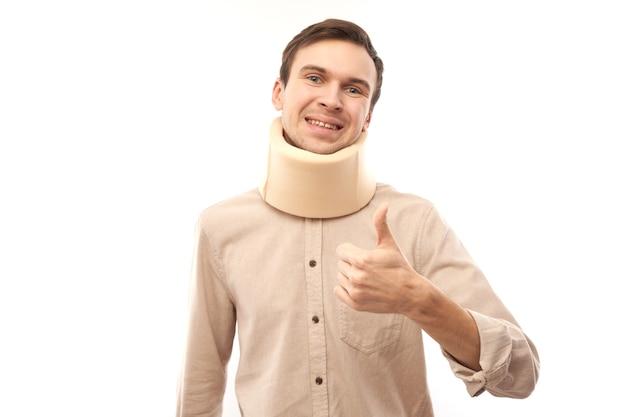 Портрет кавказского мужчины с повязкой на шее, показывая большие пальцы руки вверх, изолированные, травмы и переломы