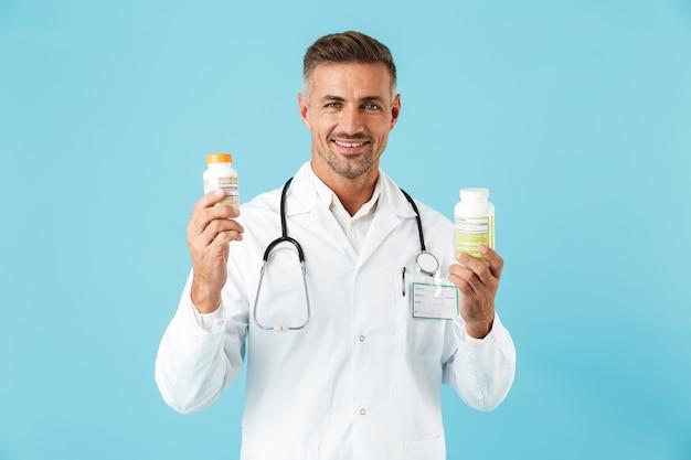 青い壁の上に孤立して立って、錠剤の瓶を保持している白いコートを着ている白人の医療専門家の肖像画