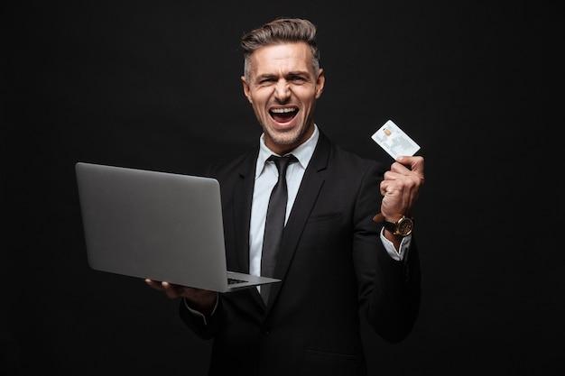 Портрет кавказского кричащего бизнесмена, одетого в формальный костюм, держащего портативный компьютер и кредитную карту, изолированную над черной стеной