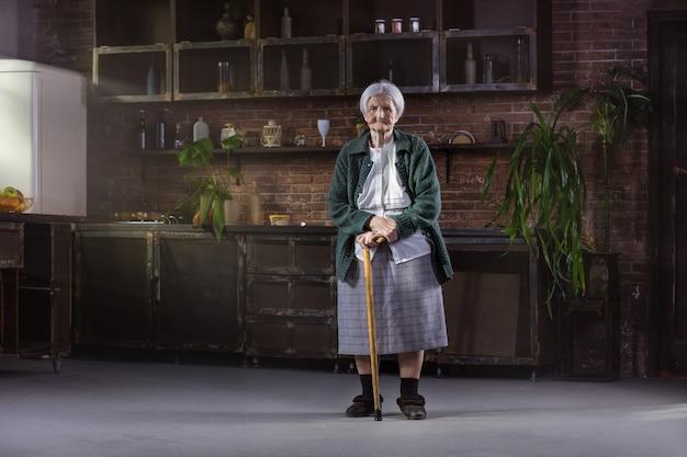 自宅で杖を持つ白人の年配の女性の肖像画
