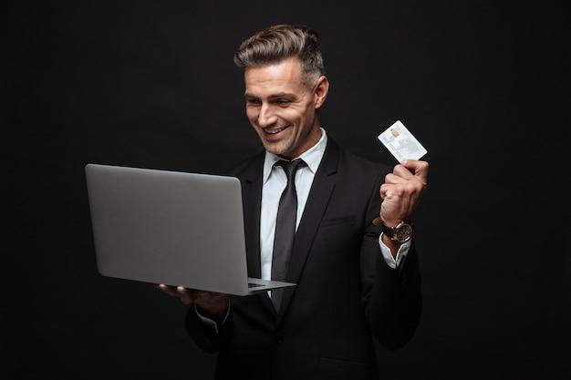 Портрет кавказского улыбающегося бизнесмена, одетого в формальный костюм, держащего портативный компьютер и кредитную карту, изолированную над черной стеной