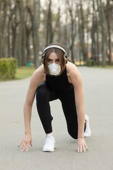 공원에서 실행하는 동안 의료 보호 얼굴 마스크를 쓰고 백인 스포티 한 여자의 초상화. 코로나 바이러스 또는 covid-19는 전 세계에 퍼져 있습니다.