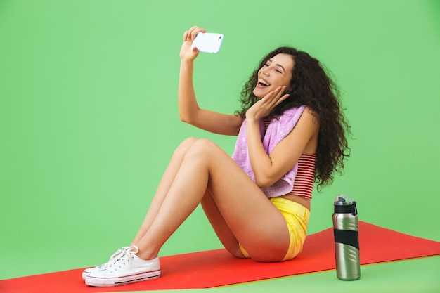 녹색 벽에서 운동한 후 피트니스 매트에 앉아 셀카 사진을 찍는 목에 수건을 두른 운동복을 입은 20대 백인 여성의 초상화