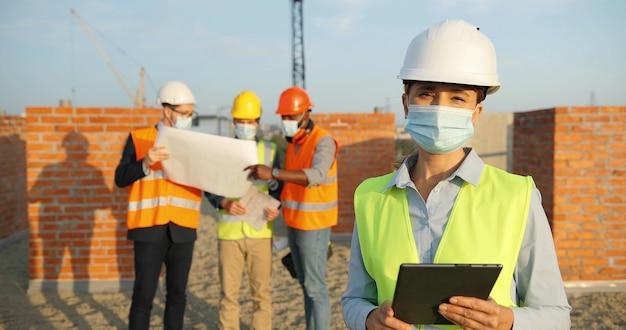 建設時に屋外に立っているカスクと医療マスクの白人女性コンストラクターの肖像画。タブレットデバイスを手にヘルメットをかぶった女性ビルダーまたはエンジニア。コロナウイルスパンデミック