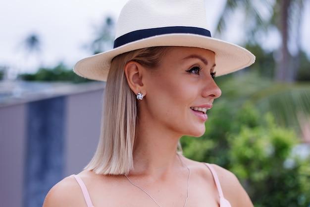 놀라운 열대 야자수와 럭셔리 풍부한 빌라 호텔에서 휴가 로맨틱 우아한 핑크 긴 드레스에 백인 여자의 초상화는 고전적인 흰색 모자에 여성을 볼 수