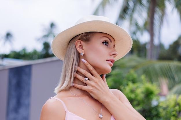 Портрет кавказской женщины в романтическом элегантном розовом длинном платье на отдыхе в роскошном роскошном отеле-вилле с потрясающим видом на тропические пальмы женщина в классической белой шляпе