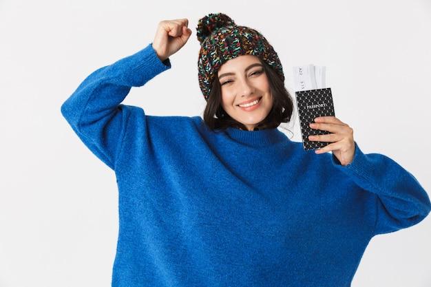 Портрет кавказской женщины в зимней шапке, держащей паспорт и проездные билеты стоя, изолированную на белом