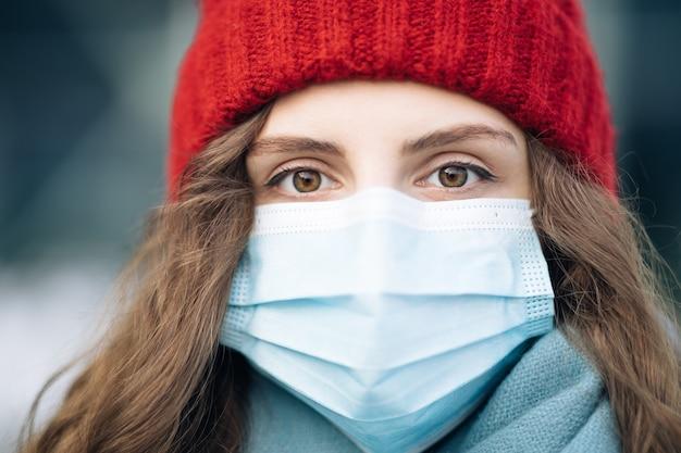 Портрет кавказской молодой курчавой женщины в медицинской маске, стоящей на зимней улице.