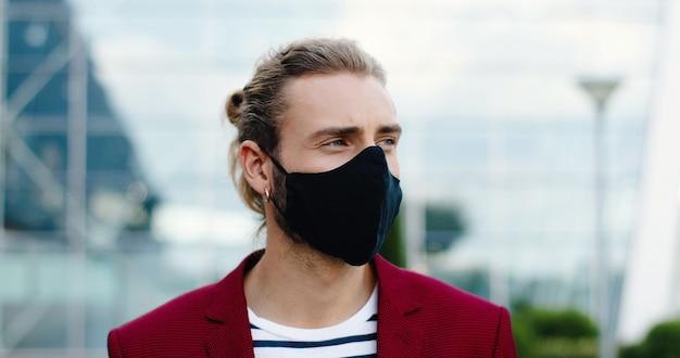 屋外でカメラを見ているマスクの白人の若いハンサムな男の肖像画。通りで耳にイヤリングを持つスタイリッシュな格好良い男性の顔のクローズアップ。コロナウイルスのパンデミックの概念。社会的距離