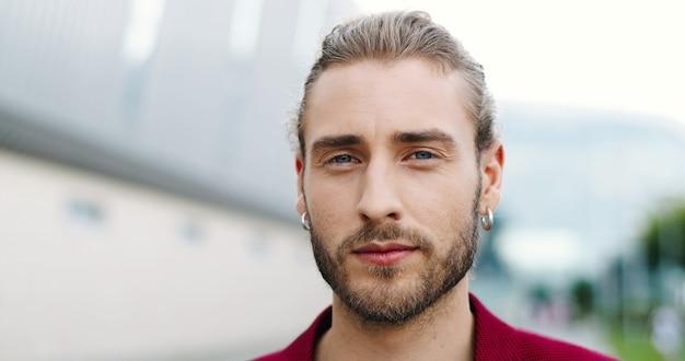 屋外でカメラを見ているひげを持つ白人の若いハンサムな男の肖像画。通りで耳に2つのイヤリングを持つスタイリッシュな格好良い男性の顔のクローズアップ。