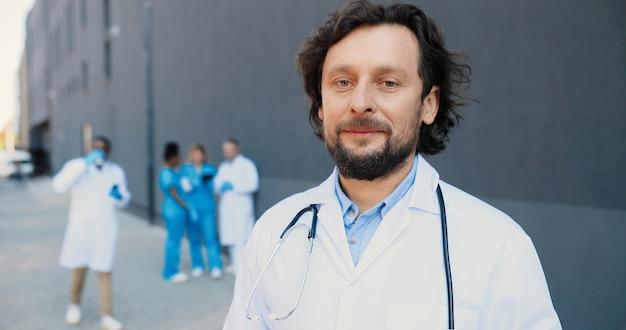 Портрет доктора молодого человека кавказа со стетоскопом смотря камеру и усмехаясь. красивый мужчина улыбка врача. многонациональные врачи на фоне. медик в белом халате в больнице.