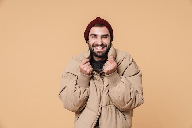 Портрет кавказского молодого человека в зимней куртке и шляпе, улыбаясь изолирован на бежевом